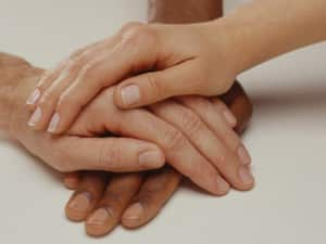Three hands on top of one another, (Close-up)